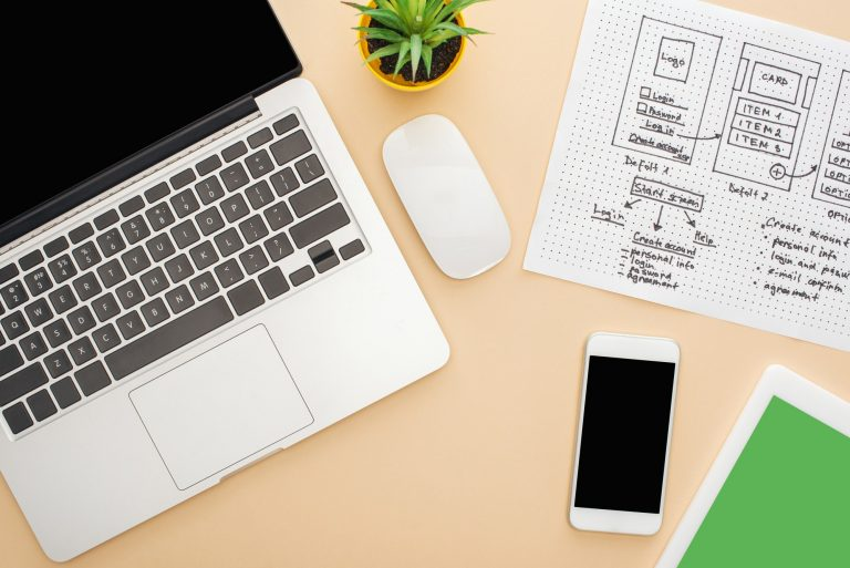 top view of gadgets near website design template and green plant on beige background